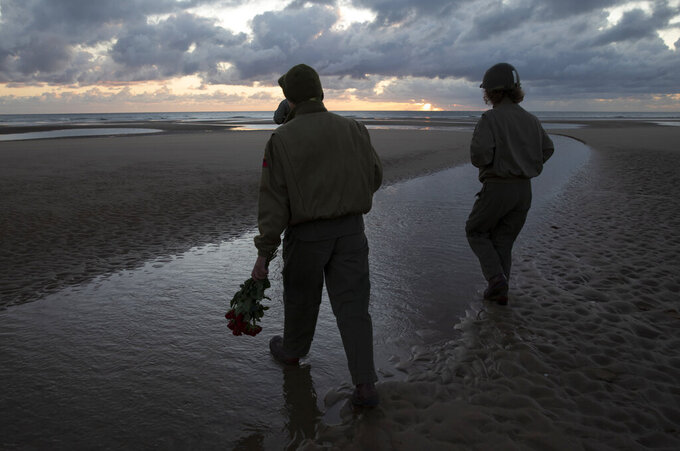 Two women in vintage US WWII uniforms walk with flowers to lay in the sea during a D-Day 76th anniversary ceremony in Saint Laurent sur Mer, Normandy, France, Saturday, June 6, 2020. Due to coronavirus measures many ceremonies and memorials have been cancelled in the region with the exception of very small gatherings. (AP Photo/Virginia Mayo)