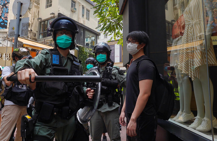 Riot police form a line as they check pedestrians gathered in the Central district of Hong Kong,  Wednesday, May 27, 2020. Hong Kong police massed outside the legislature complex Wednesday, ahead of debate on a bill that would criminalize abuse of the Chinese national anthem in the semi-autonomous city. (AP Photo/Vincent Yu)