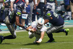 Miami Dolphins quarterback Ryan Fitzpatrick (14) falls as Seattle Seahawks outside linebacker K.J. Wright (50) and defensive tackle Bryan Mone (92) attempt to tackle, during the second half of an NFL football game, Sunday, Oct. 4, 2020, in Miami Gardens, Fla. (AP Photo/Lynne Sladky)