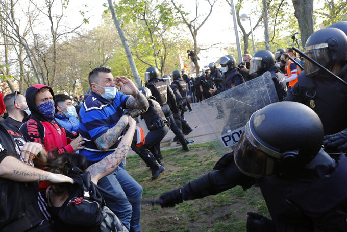 Spanish police use batons to keep protesters away from supporters of the far-right Vox party during a party rally in Madrid's Vallecas neigborhood, a traditional left-wing bastion, Spain, Wednesday, April 7, 2021. Scuffles started when the national leader of Vox, Santiago Abascal, approached a crowd which had gathered to protest the party rally. Riot peace charged the bunches of protesters to keep them away from Abascal and other members of his party campaigning for upcoming regional elections in the area including Spain's capital. (AP Photo/Bernat Armangue)