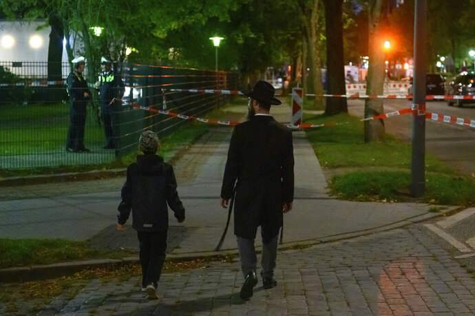 In this Sunday, Oct. 4, 2020 taken photo a man and a boy walk towards the cordoned-off area in front of the synagogue in Hamburg, Germany. The 26-year-old man was attacked as he was about to enter the grounds of the synagogue in the northern city of Hamburg on Sunday. The victim was taken to the hospital with head injuries. (Jonas Walzberg/dpa via AP)