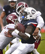 Massachusetts safety Brice McAllister, left, and Massachusetts safety Tyler Hayes, back, hit Connecticut running back Kevin Mensah during the first half of an NCAA college football game, Saturday, Oct. 27, 2018, in East Hartford, Conn. (AP Photo/Jessica Hill)