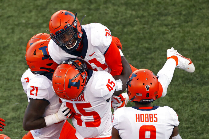Illinois defensive back Devon Witherspoon (31) celebrates with teammates after making an interception during the second half of an NCAA college football game against the Rutgers, Saturday, Nov. 14, 2020, in Piscataway, N.J. (AP Photo/Adam Hunger)