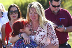 FILE- In this Feb. 14, 2018 file photo, parents wait for news after a report of a shooting at Marjory Stoneman Douglas High School in Parkland, Fla. Nikolas Cruz, a former student, was charged with 17 counts of premeditated murder. For Florida, the 2010s were a decade of high-profile mass shootings at a nightclub, high school, airport and naval base, leaving 74 victims dead. (AP Photo/Joel Auerbach, File)