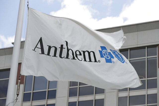 FILE - In this May 14, 2019, file photo a flag flies the outside of the corporate headquarters building of health insurance company Anthem is shown in Indianapolis. Anthem's second-quarter profit doubled to nearly $2.3 billion, as a pandemic-induced drop in claims and a new business pushed the Blue Cross-Blue Shield insurer's earnings past expectations.  But the nation's second-largest insurer left its 2020 earnings forecast unchanged, following a pattern established by its competitors. (AP Photo/Michael Conroy, File)