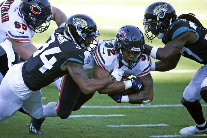 Chicago Bears running back David Montgomery (32) runs for an 8-yard gain as he is tackled by Jacksonville Jaguars cornerback Greg Mabin, left, and cornerback Tre Herndon, right, during the second half of an NFL football game, Sunday, Dec. 27, 2020, in Jacksonville, Fla. (AP Photo/Stephen B. Morton)
