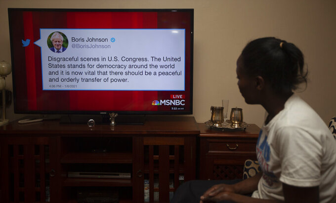 A Kenyan watches a news report on Kenyan TV, Thursday, Jan. 7, 2021, showing Britain's Prime Minister Boris Johnson Twitter comment among World leaders reaction to the U.S. Capitol demonstrations on Wednesday, Jan. 6, 2021, in Washington, USA. (AP Photo/Sayyid Abdul Azim)