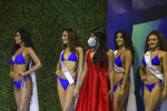 Contestants wait on the side of the stage of the Miss Nicaragua pageant, in Managua, Nicaragua, Saturday, Aug. 8, 2020. The limited audience consisted of two people per contestant spaced safely, plus a production crew of 85. The masks were off the contestants, but the judges wore them and were spaced at a safe distance. (AP Photo/Alfredo Zuniga)