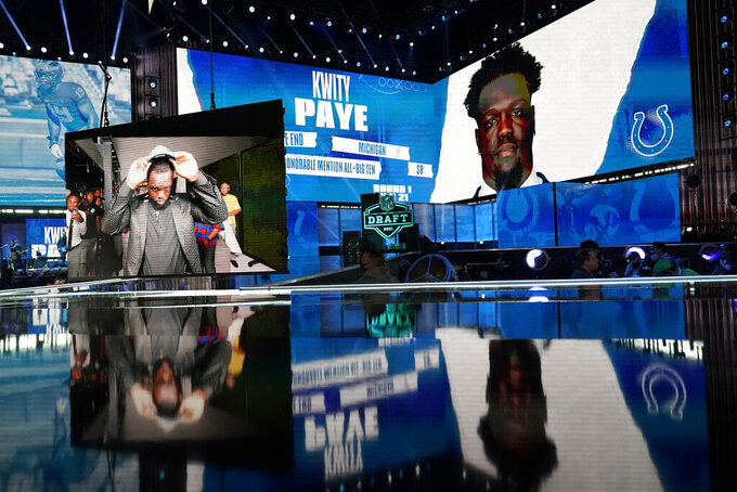 Images of Michigan defensive lineman Kwity Paye are displayed on stage after he was chosen by the Indianapolis Colts with the the 21st pick in the first round of the NFL football draft Thursday April 29, 2021, in Cleveland. (AP Photo/Tony Dejak)