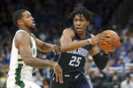 Orlando Magic's Wes Iwundu (25) looks to pass the ball as he is guarded by Milwaukee Bucks' Sterling Brown during the first half of an NBA basketball game Friday, Nov. 1, 2019, in Orlando, Fla. (AP Photo/John Raoux)