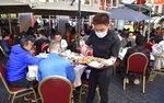 People enjoying outdoor restaurants in Chinatown, London Saturday, April 17, 2021. (AP Photo/Rui Vieira)