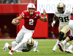 FIJLE - In this Sept. 29, 2018, file photo, Nebraska quarterback Adrian Martinez (2) carries the ball away from Purdue linebacker Derrick Barnes (55) and defensive end Kai Higgins (98) during the first half of an NCAA college football game in Lincoln, Neb. True freshman Adrian Martinez will be starting his third straight game. He's coming off his best performance after throwing for 323 yards and running for 91 against Purdue. Nebraska plays Wisconsin on Saturday.  (AP Photo/Nati Harnik, File)