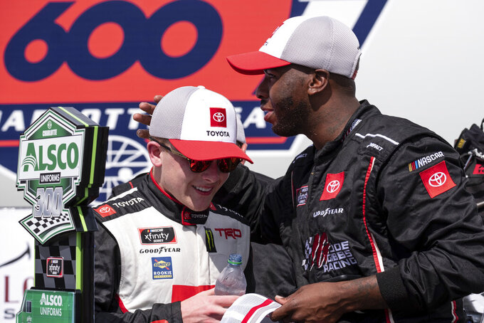 Ty Gibbs, left, celebrates with a crew member after winning the Alsco Uniforms 300 NASCAR Xfinity Series auto race at Charlotte Motor Speedway on Saturday, May 29, 2021 in Charlotte, NC. (AP Photo/Ben Gray)