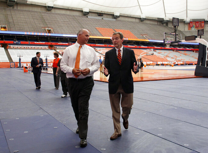 FILE - In this July 12, 2016, file photo, Syracuse University athletic director John Wildhack, right, talks with Syracuse University vice president and chief facilities officer Peter Sala, left, during a visit to the Carrier Dome in Syracuse, N.Y. Sala remembers the moment as if were yesterday, always will. It was the late 1970s, he was a high school student, and Syracuse University had decided to replace aging Archbold Stadium with an indoor facility featuring an air-supported roof. Sala's dad, John, was director of the university's physical plant, and brought some of the drawings of the future Carrier Dome home. (AP Photo/Nick Lisi, File)