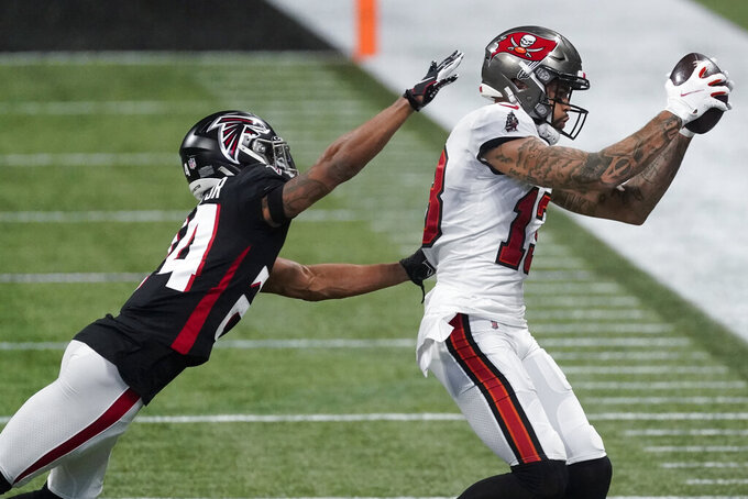 Tampa Bay Buccaneers wide receiver Mike Evans (13) makes the catch against Atlanta Falcons cornerback A.J. Terrell (24) during the first half of an NFL football game, Sunday, Dec. 20, 2020, in Atlanta. (AP Photo/John Bazemore)