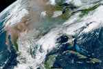This Friday, Sept. 18, 2020 satellite image made available by the National Oceanic and Atmospheric Administration shows gray smoke from wildfires in the western United States drifting across the continent and the remnants of Hurricane Sally in the southeast. In the past week, swaths of the country have been burning and flooding in devastating extreme weather disasters. (NOAA via AP)