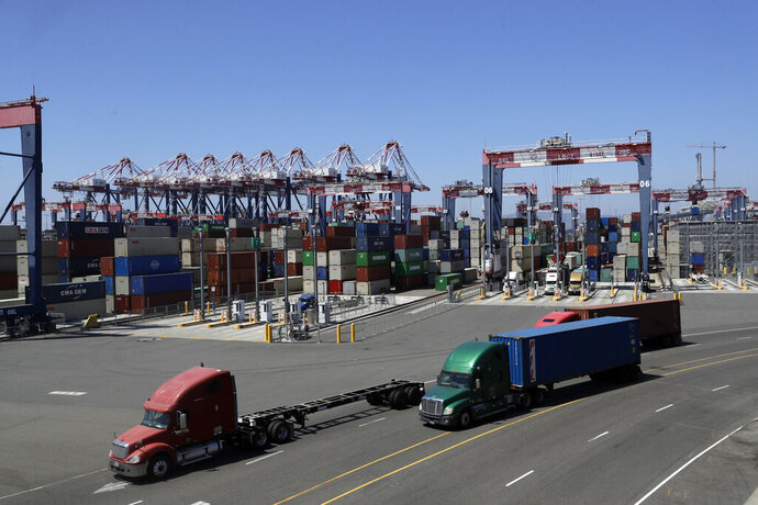 FILE - In this Aug. 22, 2018, file photo, trucks travel along a loading dock at the Port of Long Beach in Long Beach, Calif. The California Air Resources Board is scheduled to vote Thursday, June 25, 2020, on new first-in-the-nation rules to require a certain percentage of work truck sales each year must be electric vehicles. When the rule is fully implemented by 2035, the board estimates it will result in at least 20% of all delivery vans and work trucks on the road will be electric vehicles. (AP Photo/Marcio Jose Sanchez, File)