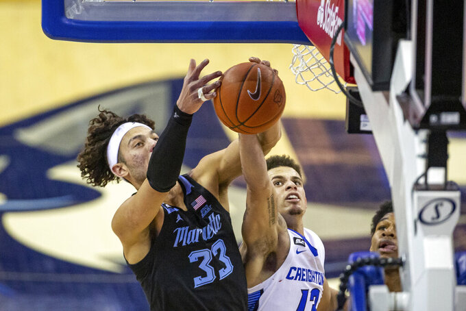 Marquette forward Dawson Garcia (33) and Creighton forward Christian Bishop (13) go for a rebound in the first half during an NCAA basketball game on Monday, Dec. 14, 2020, in Omaha, Neb. (AP Photo/John Peterson)