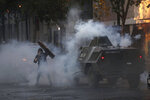 An anti-government demonstrator clashes with a police armored vehicle spewing tear gas during protests in Santiago, Chile, Tuesday, Nov. 19, 2019. Chile has been facing weeks of unrest, triggered by a relatively minor increase in subway fares. The protests have shaken a nation noted for economic stability over the past decades, which has seen steadily declining poverty despite persistent high rates of inequality. (AP Photo/Esteban Felix)