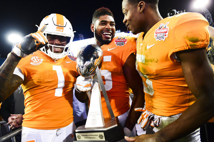 Tennessee wide receiver Jauan Jennings (15) holds the trophy next to wide receivers Marquez Callaway (1) and Josh Palmer (5) after the team's 23-22 win over Indiana in the Gator Bowl NCAA college football game in Jacksonville, Fla., Thursday, Jan. 2, 2020. (Calvin Mattheis/Knoxville News Sentinel via AP)