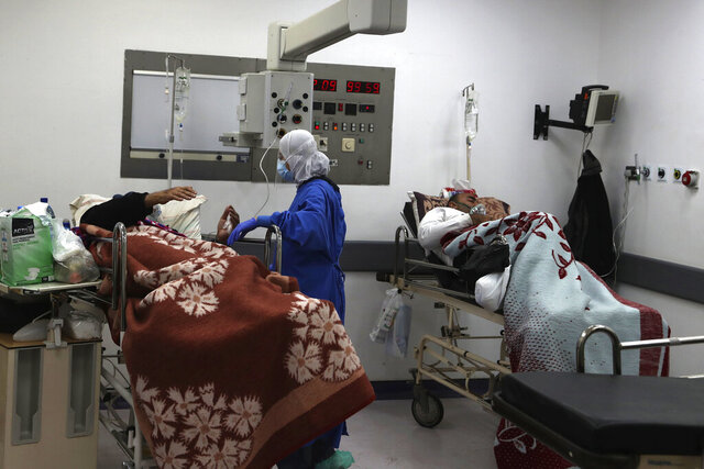 A medical staffer takes care of COVID-19 patients at the intensive care unit of the Rafik Hariri University Hospital in Beirut, Lebanon, Friday, Jan. 22, 2021. Hospitals in Lebanon are reaching full capacity amid a dramatic surge in coronavirus cases across the crisis-hit Mediterranean nation even amid strict lockdown. (AP Photo/Bilal Hussein)