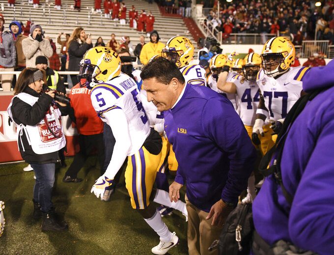 LSU coach Ed Orgeron leads the team onto the field before playing Arkansas during an NCAA college football game, Saturday, Nov. 10, 2018, in Fayetteville, Ark. (AP Photo/Michael Woods)