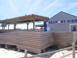 This Monday,  June 8, 2020 photo shows a Tiki bar at the Seaport Pier in North Wildwood, N.J. On June 6, 2020, the New Jersey Department of Environmental Protection said North Wildwood had demolished dunes and wetlands, built a sea wall and added buildings to the pier without required permits or review by the agency, which may make the city tear the work it did, and restore the area to its natural condition. (AP Photo/Wayne Parry)