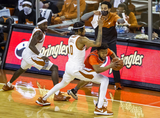 "Texas forward Gerald Liddell (0) and Texas Longhorns guard Courtney Ramey (3) defend against Ricky ""Doc"" Nelson (13) during the first half of an NCAA college basketball game, Wednesday, Nov. 25, 2020 in Austin, Texas. (Ricardo B. Brazziell/Austin American-Statesman via AP)"