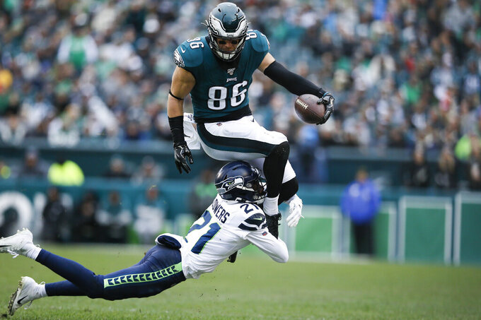 Philadelphia Eagles' Zach Ertz (86) leaps over Seattle Seahawks' Tre Flowers (21) during the first half of an NFL football game, Sunday, Nov. 24, 2019, in Philadelphia. (AP Photo/Michael Perez)