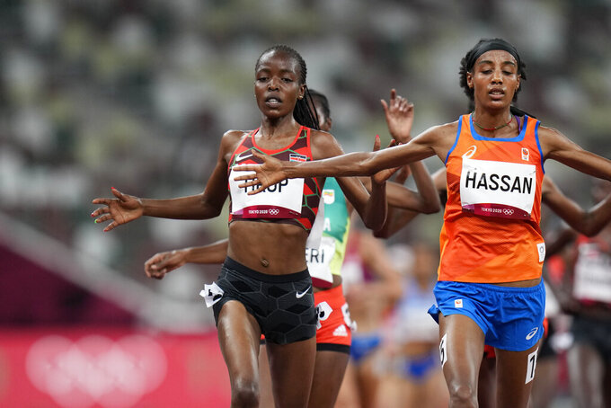 FILE - In this Friday, July 30, 2021 file photo, Sifan Hassan, of the Netherlands, right, crosses the finish line ahead of Agnes Tirop, of Kenya, left, to win a heat in the women's 5,000-meter run at the 2020 Summer Olympics, in Tokyo. Kenyan runner Agnes Tirop, a two-time world championships bronze medalist, has been found dead at her home in Iten in western Kenya, the country's track federation said Wednesday, Oct. 13, 2021. (AP Photo/Petr David Josek, File)