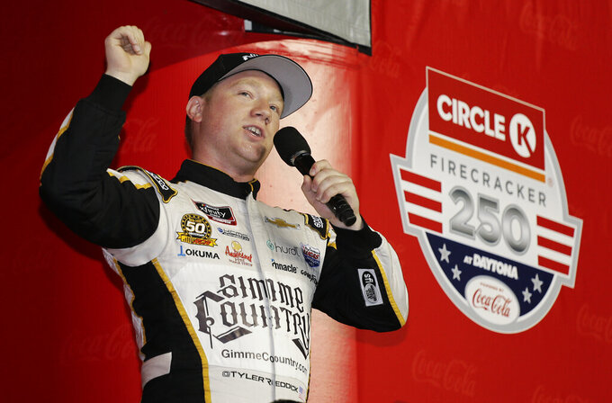 Pole sitter Tyler Reddick waves to fans during driver introductions before a NASCAR Xfinity Series auto race at Daytona International Speedway, Friday, July 5, 2019, in Daytona Beach, Fla. (AP Photo/Terry Renna)