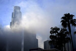 FILE - In this Dec. 10, 2015, file photo, the U.S. Bank Tower building is seen through dense fog over downtown Los Angeles. The U.S. Bank Tower, one of the tallest buildings in the West and a landmark in downtown Los Angeles, will be sold to the developer of the new World Trade Center in New York. The deal will close in September 2020. (AP Photo/Richard Vogel, File)