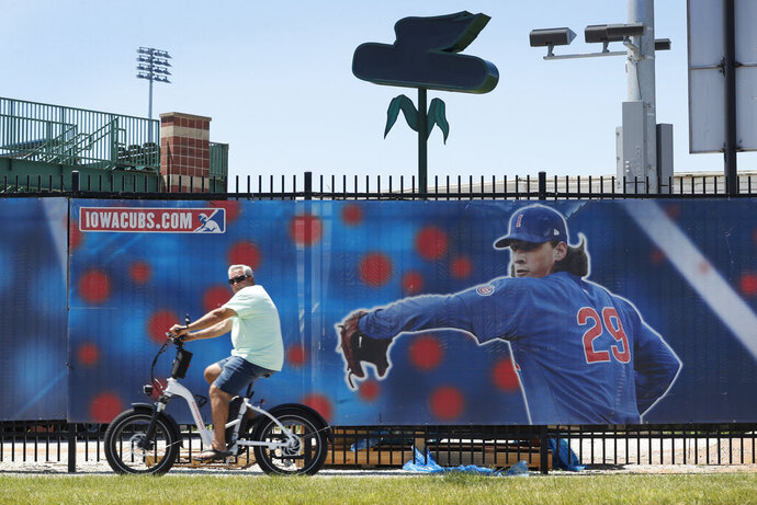 A cyclist rides past Principal Park, home to the Triple-A minor league baseball Iowa Cubs, Thursday, June 25, 2020, in Des Moines, Iowa. Two high school baseball games scheduled for Thursday at the stadium were postponed after officials said a ballpark staff member tested positive for coronavirus. (AP Photo/Charlie Neibergall)