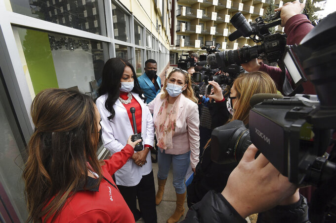 Dr. Sylvienash Moma, second from left, with hands clasped, declines to speak with the media, Monday, April 19, 2021, outside the Dr. Moma Health & Wellness Clinic at the Satellite Hotel in Colorado Springs, Colo., to address questions that the clinic allegedly improperly stored vaccines, prompting a state investigation. (Jerilee Bennett/The Gazette via AP)
