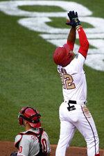 Washington Nationals' Juan Soto (22) celebrates his home run next to Philadelphia Phillies catcher J.T. Realmuto, bottom, during the second inning of a baseball game, Wednesday, Aug. 26, 2020, in Washington. (AP Photo/Nick Wass)