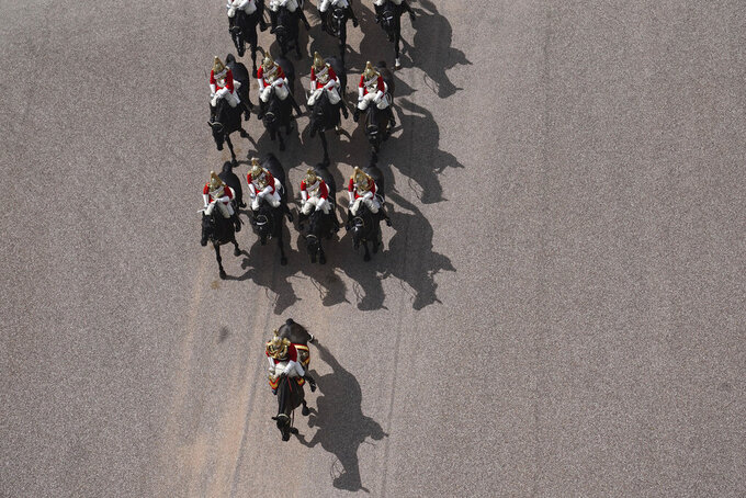 Members of the Household Cavalry arrive at Windsor Castle, Windsor, England, during a military ceremony to mark the official birthday of Queen Elizabeth II, Saturday June 12, 2021. In line with government advice The Queen's Birthday Parade, also known as Trooping the Colour, will not go ahead in its traditional form. (Steve Parsons/Pool via AP)