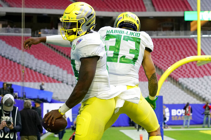 Oregon quarterback Anthony Brown celebrates his touchdown with running back Cyrus Habibi-Likio (33) during the first half of the Fiesta Bowl NCAA college football game against Iowa State, Saturday, Jan. 2, 2021, in Glendale, Ariz. (AP Photo/Rick Scuteri)