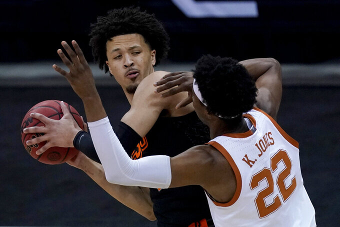Oklahoma State's Cade Cunningham looks to pass under pressure from Texas' Kai Jones (22) during the first half of an NCAA college basketball game for the Big 12 tournament championship in Kansas City, Mo, Saturday, March 13, 2021. (AP Photo/Charlie Riedel)