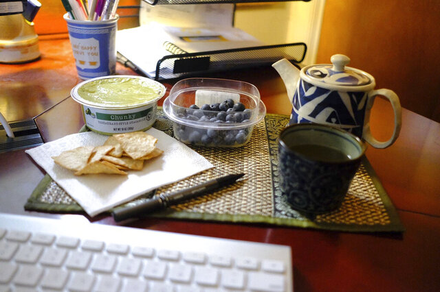 This Jan. 17, 2020 image shows a display of guacamole and chips and blueberries in Allison Park, Pa. To eat healthier in the new year, try making small and measurable changes, like bringing a healthy and  appealing snack to work. (Ted Anthony via AP)