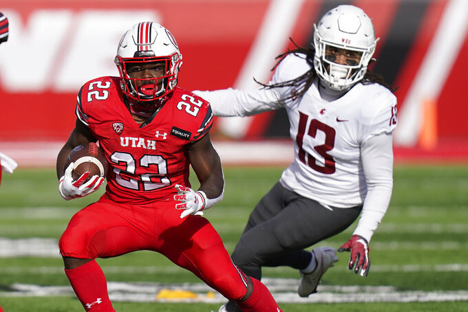 Utah running back Ty Jordan (22) runs from Washington State linebacker Jahad Woods (13) during the first half of an NCAA college football game Saturday, Dec. 19, 2020, in Salt Lake City. (AP Photo/Rick Bowmer)