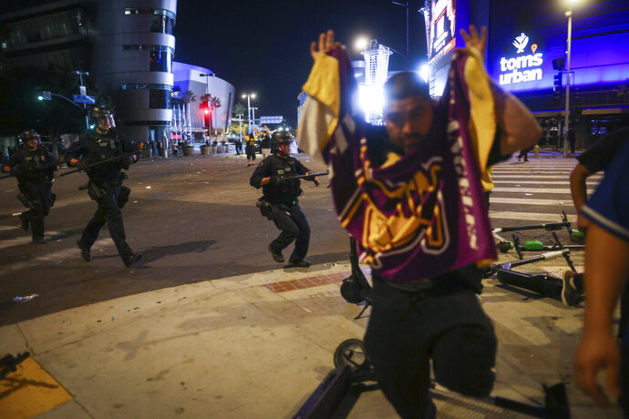Los Angeles Police officers disperse rowdy fans outside of Staples Center, Sunday, Oct. 11, 2020, in Los Angeles, after the Lakers defeated the Miami Heat in Game 6 of basketball's NBA Finals to win the championship. (AP Photo/Christian Monterrosa)