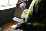 """Scolastica Apayo, sister of the late Sabina Losirkale, looks through her old photos in the Isiolo area of the Archers Post settlement in Kenya on Sunday, June 30, 2019. Scolastica said her sister finally told her the secret in 2012, two weeks before she died. """"Now that my days are over,"""" her sister told her, she could reveal all: """"When Gerald will ask you who's his father, just tell him: Father Mario."""" (AP Photo/Brian Inganga)"""