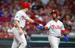 Philadelphia Phillies' J.T. Realmuto, left, is congratulated by Jean Segura after Realmuto scored on a sacrifice fly by Rhys Hoskins during the fifth inning of the team's baseball game against the Cincinnati Reds, Tuesday, Sept. 3, 2019, in Cincinnati. (AP Photo/Gary Landers)
