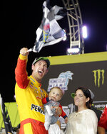 Joey Logano waves a checkered flag as he stands with his wife Brittany Baca and son Hudson after winning NASCAR Cup Series Championship auto race at the Homestead-Miami Speedway, Sunday, Nov. 18, 2018, in Homestead, Fla. (AP Photo/Terry Renna)