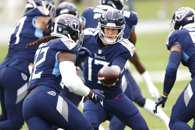 Tennessee Titans quarterback Ryan Tannehill (17) hands off to running back Derrick Henry (22) in the first half of an NFL football game against the Houston Texans Sunday, Oct. 18, 2020, in Nashville, Tenn. (AP Photo/Wade Payne)
