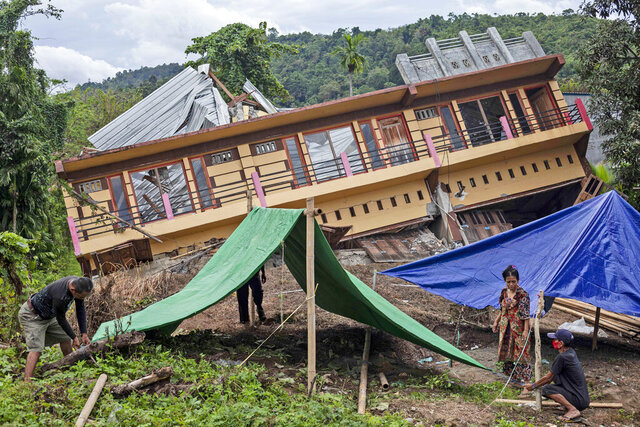 Residents build tents outside their house badly damaged by earthquake in Mamuju, West Sulawesi, Indonesia, Tuesday, Jan. 19, 2021. Aid was reaching the thousands of people left homeless and struggling after an earthquake that killed a number of people struck early Friday. (AP Photo/Yusuf Wahil)