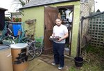 Melvin Burton holds a tray of tinned food outside his garden shed in Littleport, Cambridgeshire, England, Friday March 1, 2019. For almost as long as Britain and the European Union have been wrangling over Brexit, Burton has been preparing for a bumpy landing. He's growing vegetables, drying fruit and buying in bulk. He reels off the cornucopia of cans filling his shed and the cupboard under his stairs:
