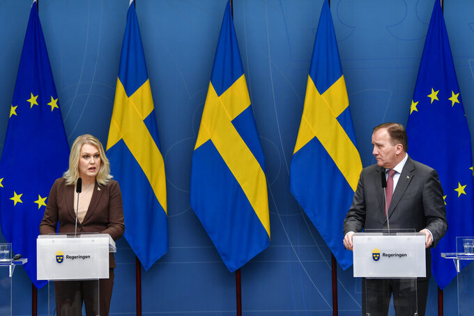 Sweden's Minister for Health and Social Affairs Lena Hallengren, left, and Prime Minister Stefan Lofven give a news conference on new restrictions to curb the spread of the coronavirus pandemic, in Stockholm, Sweden, Wednesday Nov. 11, 2020. The Swedish government proposes a stop the sale of alcohol after 10 pm from Nov. 20 until the end of February. (Henrik Montgomery / TT via AP)