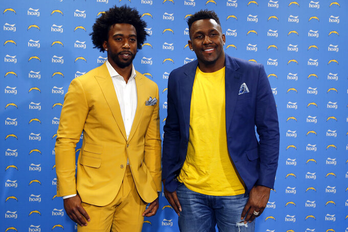 Los Angeles Chargers quarterback Tyrod Taylor, left, and linebacker Thomas Davis, right, poses for a photo during a news conference at the NFL football team's headquarters Friday, March 15, 2019, in Costa Mesa, Calif. Taylor and Davis both are signed to a two-year contract with the Chargers, the team announced Wednesday. (AP Photo/Gregory Bull)