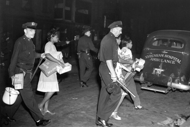 Police lead women to patrol cars in the Harlem area of New York, on Aug. 2, 1943, during clashes with police following the shooting of a policeman and six civilians. The unrest was sparked by the shooting of a black soldier by a white policeman. (AP Photo)
